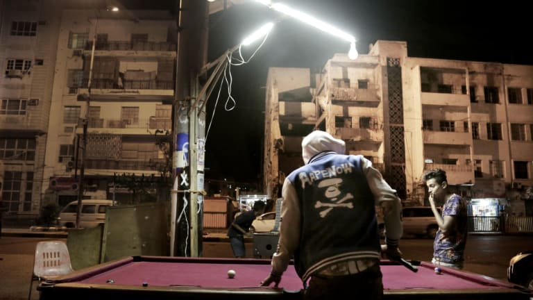 Young people play pool on a street in front of damaged buildings in Aden.