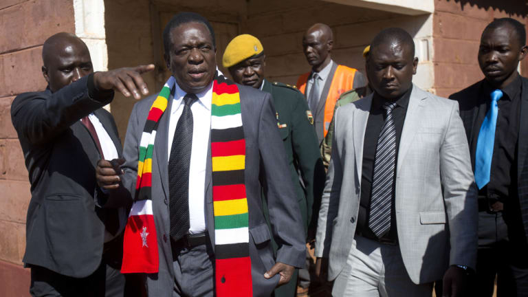 Zimbabwean President Emmerson Mnangagwa, in a scarf, leaves the polling station after casting his vote in Kwekwe.