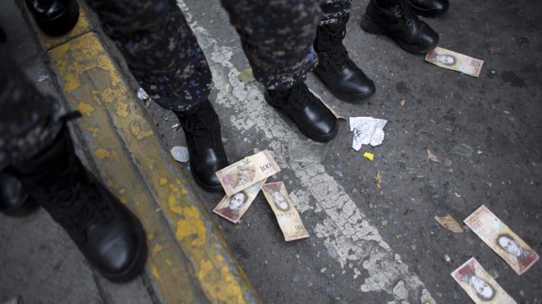 One hundred Bolivar bills lay on the ground close to the boots of several police officers, after they were thrown by protesters during a protest against the government of President Nicolas Maduro, in Caracas, Venezuela.