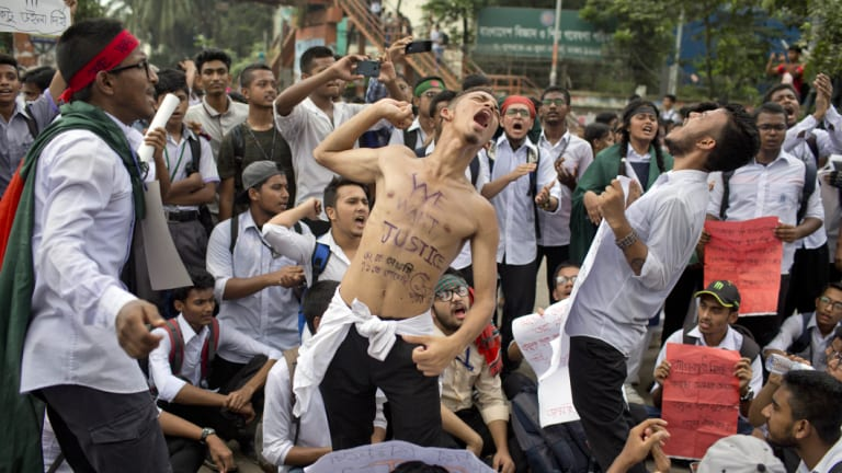 Students shout slogans and block a road during a protest in Dhaka on Saturday.