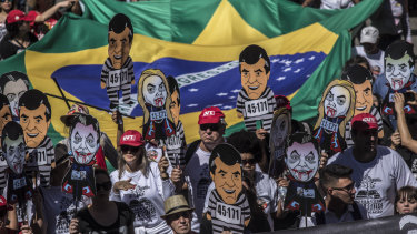Demonstrators hold banners depicting local politicians during a rally against local government officials and in support of Brazil's former president Lula, now jailed.