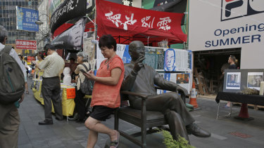 A woman plays on her phone next to a statue of the late Chinese Nobel Peace laureate Liu Xiaobo in Hong Kong.