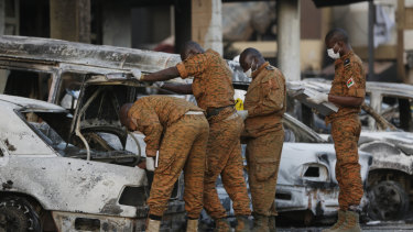 Soldiers examine burnt-out cars outside the Splendid Hotel in Ouagadougou, Burkina Faso, in 2016.