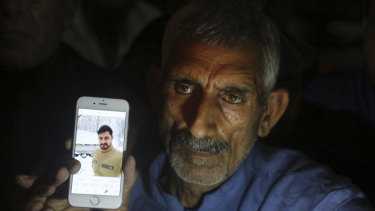 Pakistan's Mohammad Aslam shows a picture of his son Taimoor Aslam, who he said lost his life at the Kashmir border (Line of Control) on Thursday.