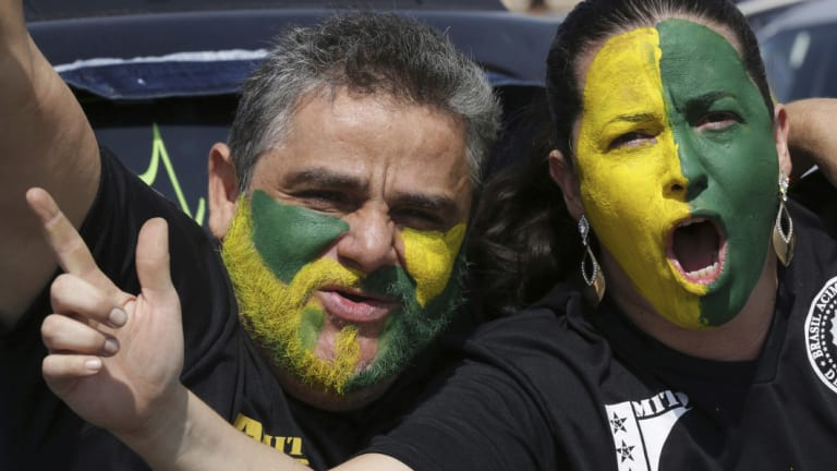 With their faces painted with the colours of Brazil, demonstrators shout slogans during a race in support of Jair Bolsonaro.