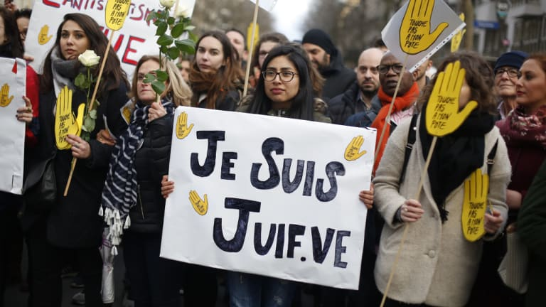 """A woman carries a poster reading """"I am a jew"""" as she attends a silent march to honour an 85-year-old woman who escaped the Nazis 76 years ago but was stabbed to death in her Paris apartment in March, apparently because she was Jewish."""