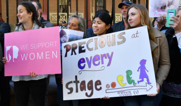 Anti-abortion protesters hold signs during a rally outside NSW Parliament.
