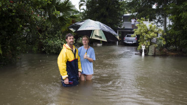 Local resident Paul Shafer and daughter Lily standing in floodwaters in Hermit Park, Townsville, on Saturday. They made the decision to evacuate later in the day.