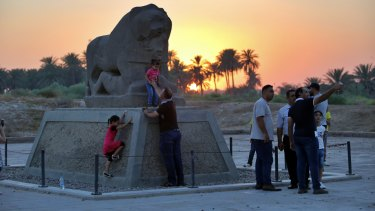 People stand near the Lion of Babylon at the archaeological site of Babylon, Iraq, on Friday.