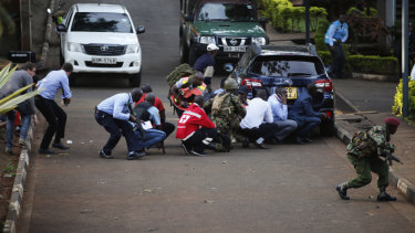 People take cover after an attack on a hotel in Nairobi on Tuesday.