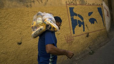 With a mural depicting the eyes of Veneuzela's late President Hugo Chavez, Carlos Gonzales carries a bag with food delivered by the government for the poorest people in the Antimano neighbourhood of Caracas, Venezuela.