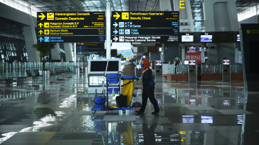 A cleaner walks through the nearly empty Soekarno-Hatta International Airport in Jakarta, Indonesia.