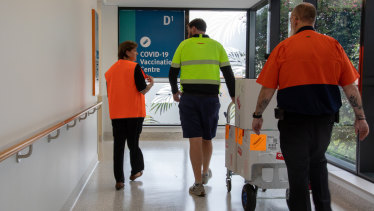 Gold Coast University Hospital Pharmacy director Liz Coombes chaperones the Pfizer vaccine into the hospital on Sunday.