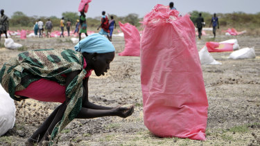 A woman scoops fallen sorghum grain off the ground after an aerial food drop by the World Food Programme in the town of Kandak, South Sudan.