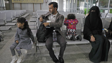 A Yemeni family waits in the departure hall at Sanaa International airport for a UN flight on Monday.