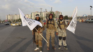 Taliban fighters hold flags in Kabul, Afghanistan.