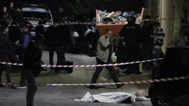 Police officers stand over the body of Greek-Australian John Macris who was shot dead outside his house in southern Athens.