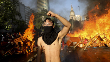 An anti-government protester stands guard at a burning barricade in Santiago, Chile, on Monday.