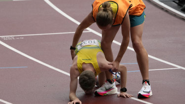 Jaryd Clifford collapses after his marathon and is assisted by his guide Tim Logan.