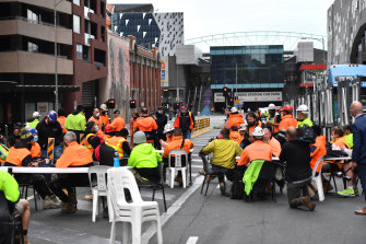 Construction workers protest the ban on tearoom gatherings, blocking Lonsdale Street during their lunch break.