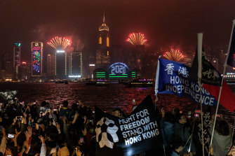 Pro-democracy supporters wave flags and shout slogans during a countdown party in Hong Kong.