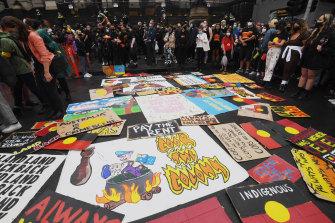 Para pengunjuk rasa meletakkan tanda di depan Gedung Parlemen.