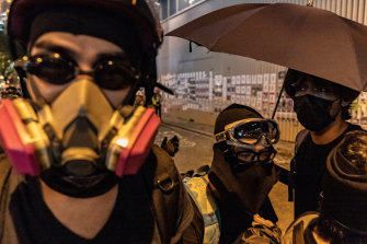 Protesters wearing tear gas masks hold umbrellas during a stand-off outside the Central Government Complex in Hong Kong.