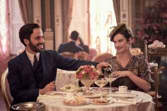 """""""Those 'bright young things' between the wars were really 'out there' people"""": Fabrice De Sauveterre (Assaad Bouab) and Linda Radlett (Lily James) enjoy champagne."""