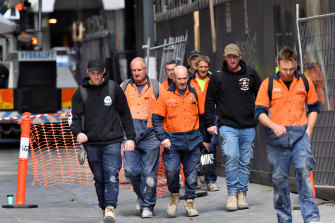 Knock off time: construction workers leave a city building site on Tuesday with far less than the advised 1.5 metres between them.