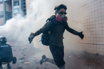 A protester flees through a cloud of tear gas in an attempt to leave Hong Kong's Polytechnic University this week.