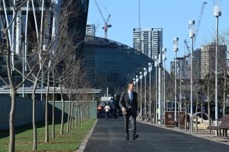 Planning and Public Spaces Minister Rob Stokes paces the tree-lined walkway at Barangaroo.