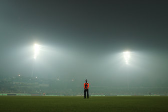 A security guard stands sentry amid smoke haze at Manuka Oval in Canberra.