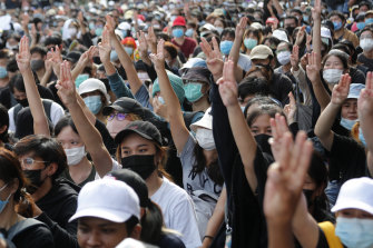Pro-democracy students raise three-fingers, symbol of resistance salute, during a rally in Bangkok on August 16.