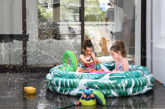 Florence and Grace Scotting cool off in their paddling pool at Balmain on the second day of a record breaking November heatwave.
