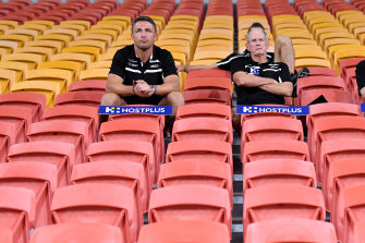 Rugby league in the coronavirus age: Souths' Sam Burgess, Jason Demetriou and Wayne Bennett swap the coaches' box for the grandstand at Suncorp Stadium on Friday night.