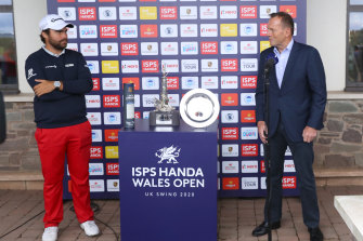 Former Australian PM Tony Abbott, right, presents the Wales Open trophy to Romain Langasque, of France, at the Celtic Manor Resort in Newport, Wales.
