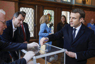 French President Emmanuel Macron casts his ballot in the mayoral elections on Sunday.
