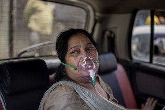 A COVID-19 patient sits inside a car and breathes with the help of oxygen provided by a Gurdwara, a Sikh house of worship, in Delhi, India.