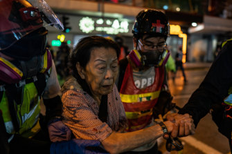 Volunteer medics help a woman cross a road during a clash between police and protesters in Causeway Bay district in Hong Kong.