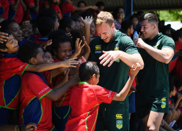 Rock stars: Prime Minister's XIII stars Daly Cherry-Evans and Nick Cotric are mobbed by local schoolchildren.