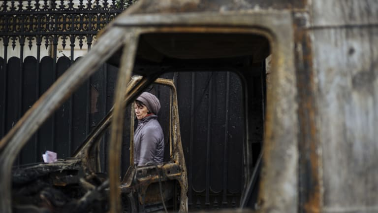 A woman and a burned out vehicle, near the Arc de Triomphe, in Paris, on Sunday, local time.