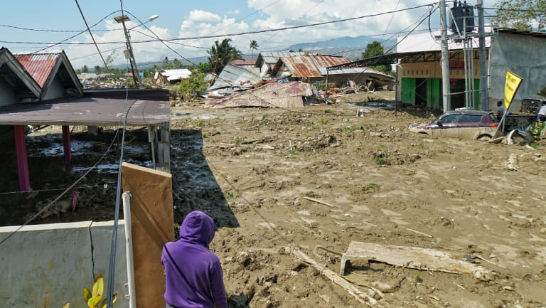 A man looks at the chaos left by the broken water embankment in Petobo, a district of Palu. A strong smell of decay is in the air, as locals says many of the victims are still trapped underneath the mud following the tsunami.