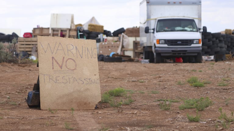 A sign stands outside the remote desert location where a family were allegedly teaching their children to be mass shooters.