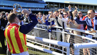 James McDonald shows off his trophy for The Everest to the crowd at Randwick on Saturday