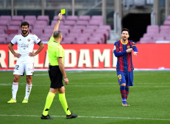Lionel Messi of Barcelona is shown a yellow card after removing his shirt.