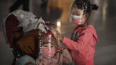 Chinese children wear plastic bottles as protective masks while waiting to check in to a flight in Beijing.