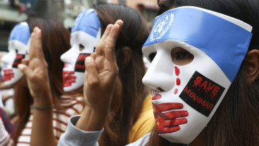 Young demonstrators wear masks to protest China's blocking of sanctions at the United Nations security council.