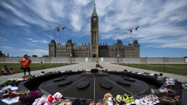 Shoes line the edge of the Centennial Flame on Parliament Hill in memory of the 215 children whose remains were found.