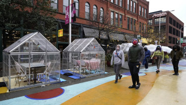 People walk by outdoor plastic dining bubbles on Fulton Market in Chicago.