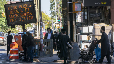 A traffic sign asks people to keep socially distant on New Utrecht Avenue in the Orthodox Jewish neighbourhood of Borough Park in Brooklyn.
